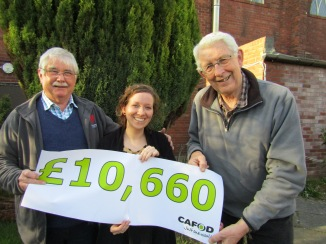 Mike Dooling and Mike Merriman celebrate last year's Fun Run total with CAFOD's Colette Byrne